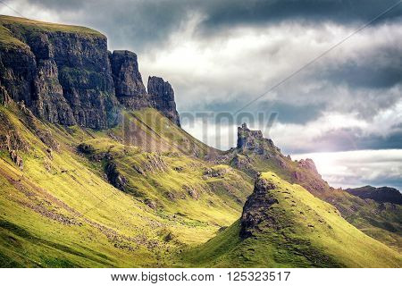 Scenic view of Quiraing mountains, with dramatic sky in the Isle of Skye, Scottish highlands, United Kingdom. Cinematic style processing with lens flare.