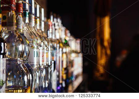 GRODNO BELARUS - NOV 7 2015: Blurred alcohol bottles on a bar at the gastrobar HOUDINI in Grodno Belarus November 7 2015