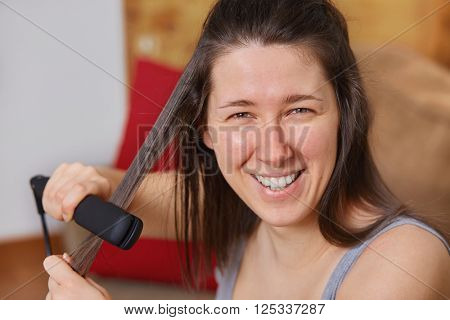Young woman using hair straightener