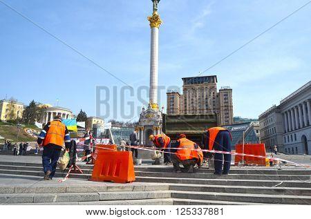 : Utility workers in orange vests repair after riot and vandalism 2013-2014. Khreshatik - central street of Kiev.At April 8,2016 in Kiev, Ukraine