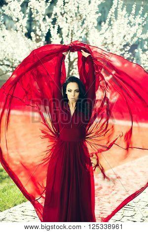 Girl In Red Dress Near Blossom