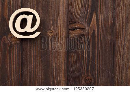 Wooden e-mail symbol on grunge wood background