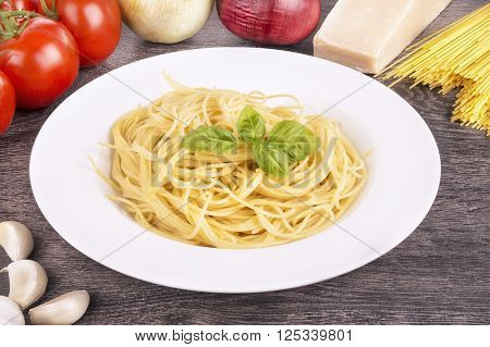Plate of cooked spaghetti pasta. Wooden plank in background.