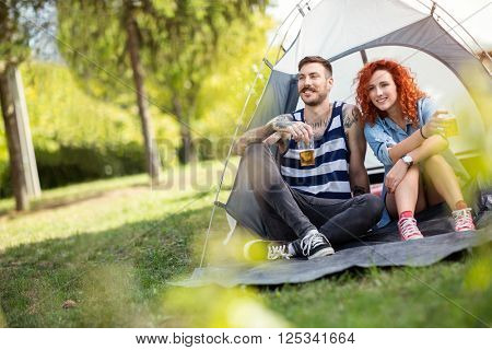 Young couple in front of tent at at music summer camp festival