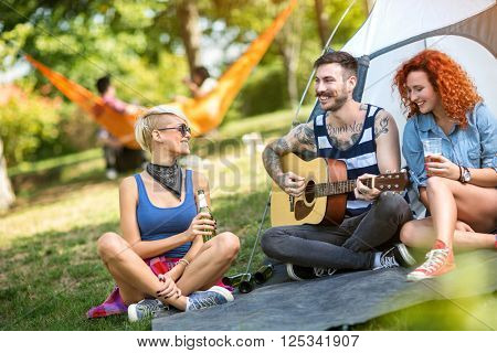 Young tattoo guy play guitar while girls enjoys in music and cold beer at summer camp