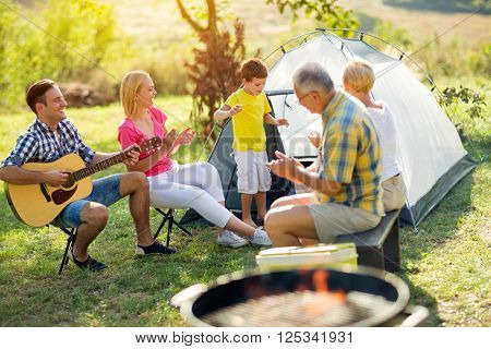 child singing with smiling family on camping