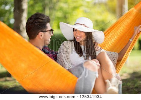 Young guy with nice smiling girlfriend in orange hammock in woods