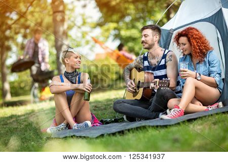 Young people enjoys on excursion with beer and guitar at camp in forest