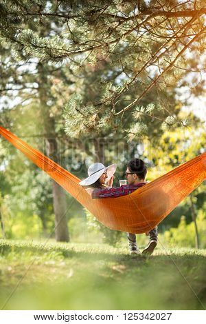 Romantic couple in hammock photographed from behind in forest