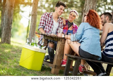 Girls and guys sits on bench at wooden table in forest, drink beer and make jokes