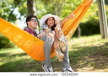 Couple in orange hammock  look something in distance in nature