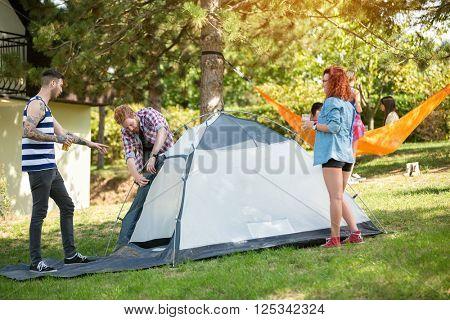Young people raising blue ten in woods