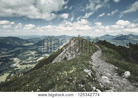 Young hikers holding hands and enjoying beautiful alpine valley standing on top of mountain - adventure concept
