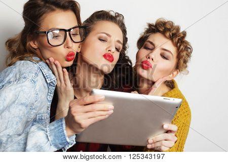 three teen girls friends taking selfie with digital tablet