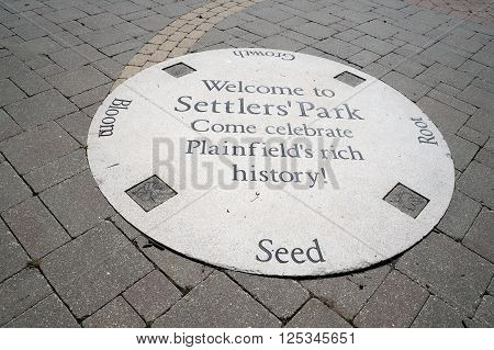 PLAINFIELD, ILLINOIS / UNITED STATES - SEPTEMBER 20, 2015: A sign on a brick sidewalk welcomes people to Settlers' Park in Plainfield.
