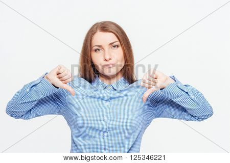 Young woman showing thumbs down isolated on a white background