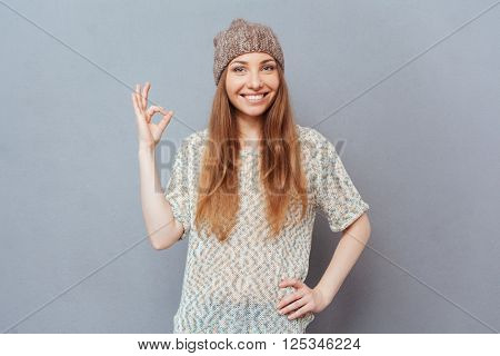 Happy woman showing ok sign with fingers and looking at camera over gray background