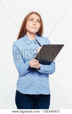 Young pensive woman with clipboard standing isolated on a white background