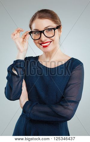 Smiling charming woman in glasses looking at camera isolated on a white background