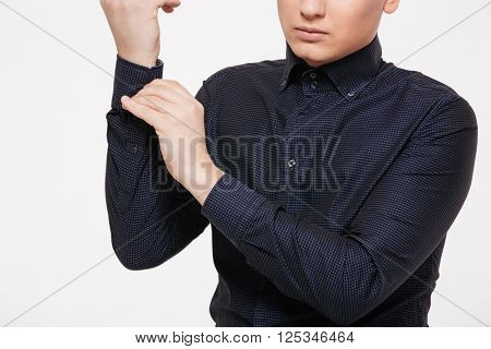 Cropped image of a man buttoning his shirt isolated on a white background
