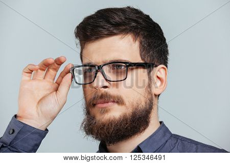 Handsome man in glasses looking away isolated on a white background
