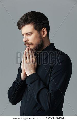Businessman praying over gray background
