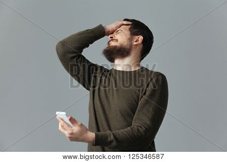 Stressed man holding smartphone over gray background