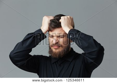 Stressed businessman standing over gray background
