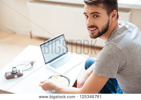 Smiling handsome young man using laptop and eating cerials with milk at home