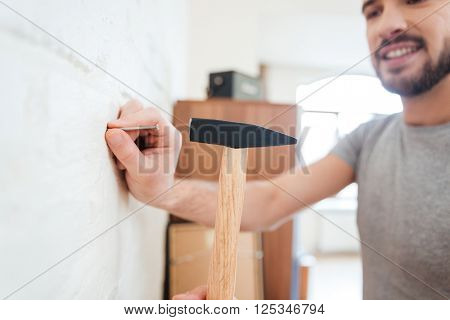 Smiling attractive young man hammering nail on white wall