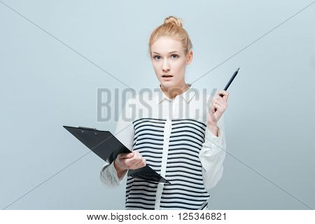 Pensive young woman holding clipboard isolated on a white background