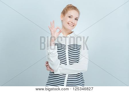 Smiling woman showing ok sign isolated on a white background