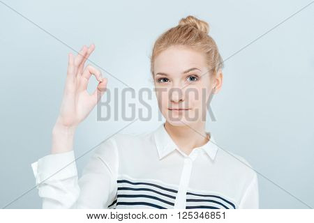 Blonde woman showing ok sign with fingers isolated on a white background
