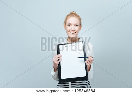Smiling casual woman showing blank clipboard isolated on a white background