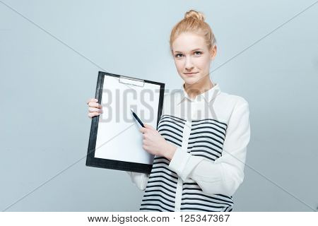 Young woman showing blank clipboard isolated on a white background