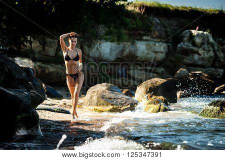 Young woman in black bikini walks on a rocky sea coast