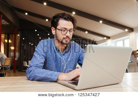 Casual man sitting at the table with laptop computer in office
