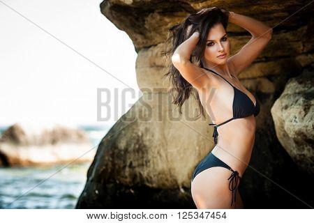 Young woman in black bikini posing on a sand rocks near the sea