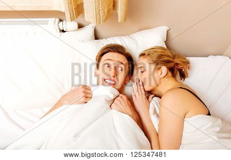 Woman whispering to her husband and he laughting
