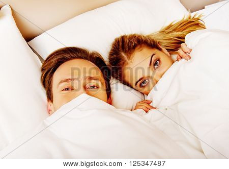 Young funny couple lying on bed with quilt on faces
