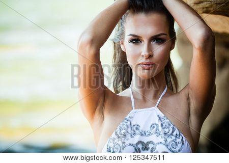 Young woman in bikini posing on a sand rocks near the sea