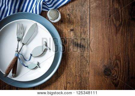 Sea food place setting on wooden table with copy space. Menu card for restaurants