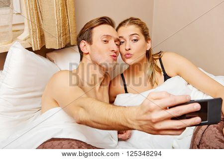 Young couple making selfie while lying in bed