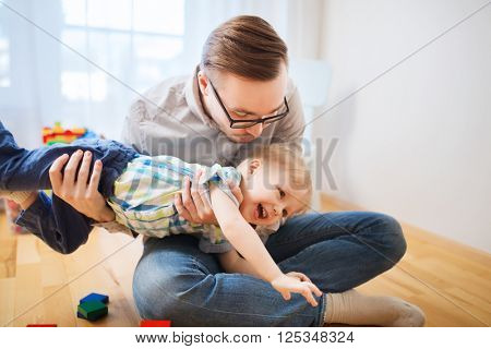 family, childhood, fatherhood, leisure and people concept - happy father and little son playing and having fun at home