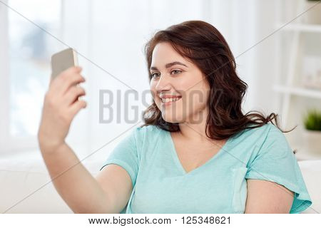 people, technology, communication and leisure concept - happy young plus size woman taking selfie with smartphone at home