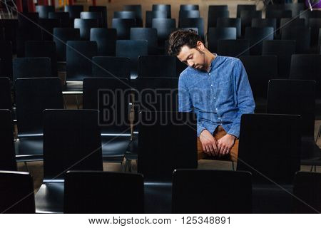 Young man sleeping in conference hall