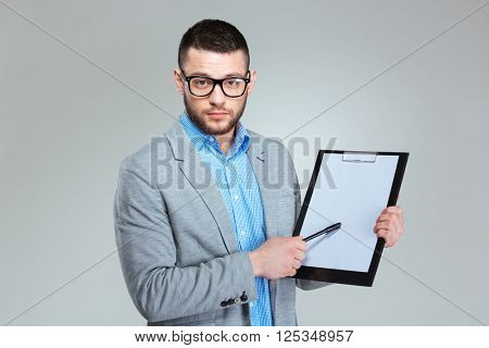 Businessman showing blank clipboard over gray background