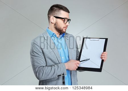 Handsome businessman showing blank clipboard over gray background