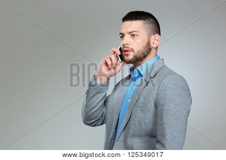 Businessman talking on the phone over gray background