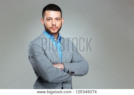 Serious businessman standing with arms folded over gray background and looking at camera